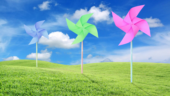 Paper toy windmill in green grass field