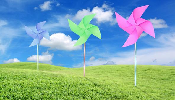 Paper toy windmill in green grass field